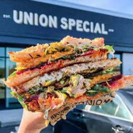 A colorful, loaded sandwich with multiple layers