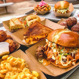 Several trays of mouthwatering Southern food, from BBQ sandwiches to mac n cheese and more