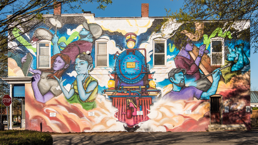 A vibrant, colorful mural of a train, with artists surrounding it
