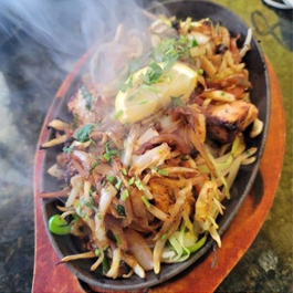A steaming dish of food on an iron skillet