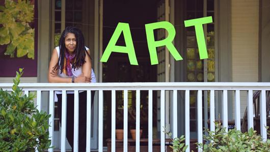 Linda Dallas on a porch next to an ART sign