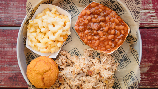 A platter with BBQ, baked beans, mac n cheese and cornbread