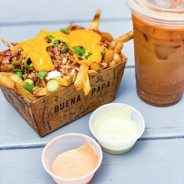 Close-up photo of loaded fries and an iced coffee