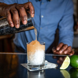 Close-up of man pouring a cocktail over ice