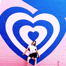 Woman in front of a giant pink and blue heart mural