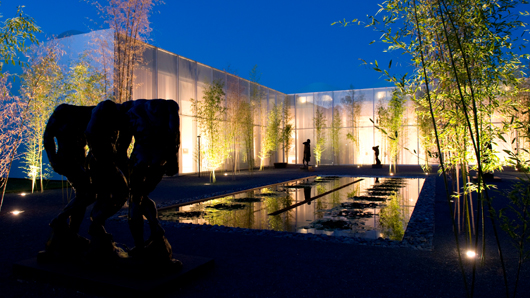 Rodin garden at the North Carolina Museum of Art at night, light reflecting off of the reflection pond
