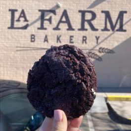 Chocolate chip cookie being held up in front of a La Farm Bakery logo mural