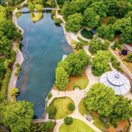 Aerial photo of Pullen Park, with a big pond and a view of the top of the historic carousel