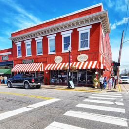 A shot of the red-painted exterior of Anna's Pizzeria on the corner of a block in downtown Apex