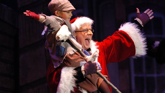 Scene from A Christmas Carol with a smiling, celebrating Scrooge and Tiny Tim