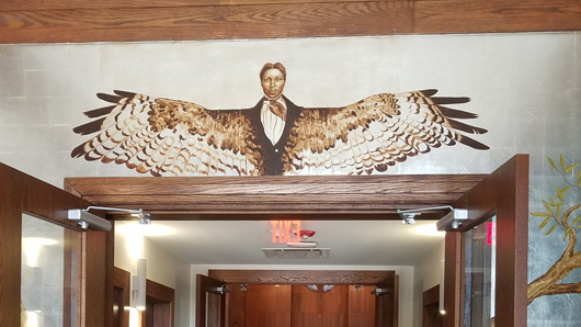 Artwork over a door of a man with bird wings