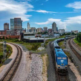 Raleigh skyline view from the Warehouse District with Raleigh Union Station and an Amtrak train in the foreground