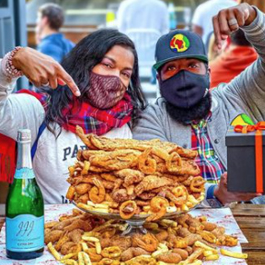 A couple in front of a massive, fried seafood platter