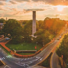 Aerial shot of the Memorial Belltower at North Carolina State University and Hillsborough St. during a sunset