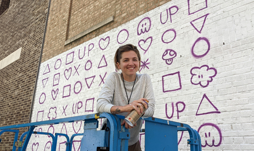 Artist Taylor White on a lift next to a large mural she worked on