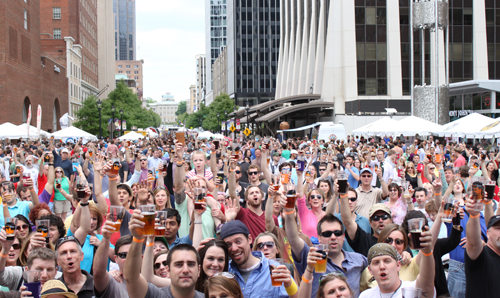 A crowd of beer drinkers raising their glasses to cheers