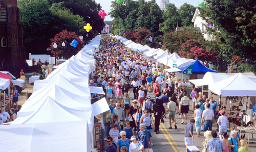 A crowd at a small-town festival with tents lining the street