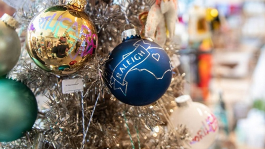 Close-up of a blue Raleigh holiday tree ball ornament