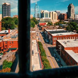 View of the downtown Raleigh skyline from a window with the pane in the foreground