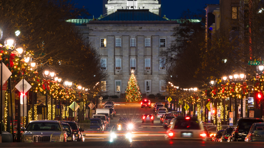 Looking down a festive Fayetteville St. towards the N.C. State Capitol with a massive holiday tree in front