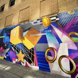 A colorful, huge outdoor mural depicting video game imagery, with coins, stars, yellow cubes with question marks and more