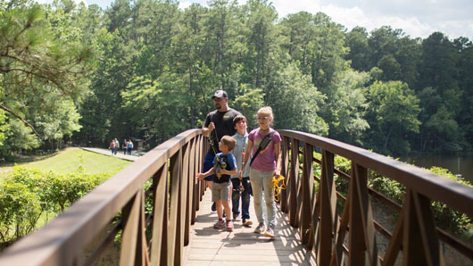 A family crossing a bridge with fishing gear at William B. Umstead State Park
