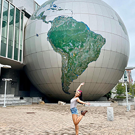 Woman posing in celebration in front of the giant globe at North Carolina Museum of Natural Sciences