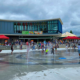A vibrant celebration with kids playing in a splash pad in front of a new-like, glass-covered building