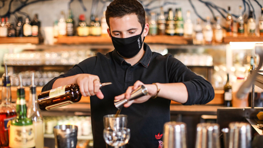 A bartender with a mask on making a cocktail