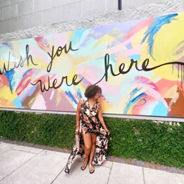 A women in front of a colorful, large outdoor mural that says Wish You Were Here