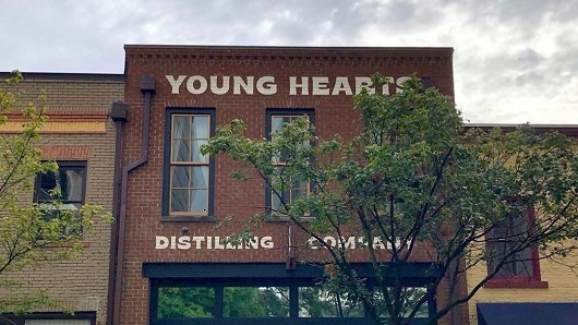 Exterior of a historic downtown building with Young Hearts Distilling Company painted in large letters