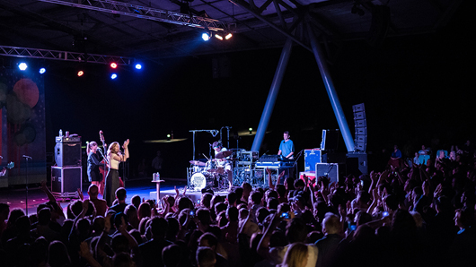 Photo of a nighttime concert in an amphitheater with a large crowd