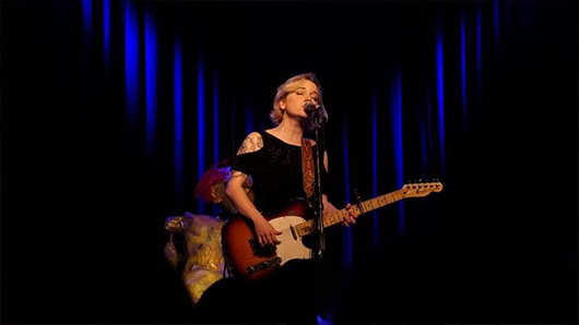Lydia Loveless singing with a guitar in front of a crowd