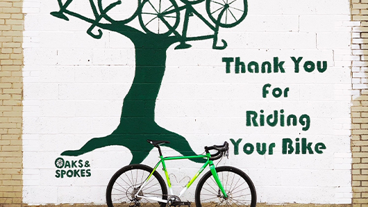 Outdoor mural of a three with bikes as its branches and that says Thank You for Riding Your Bike