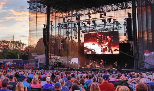 Photo of the large, outdoor Red Hat Amphitheater Main Stage taken mid-crowd, with a sunset in the background