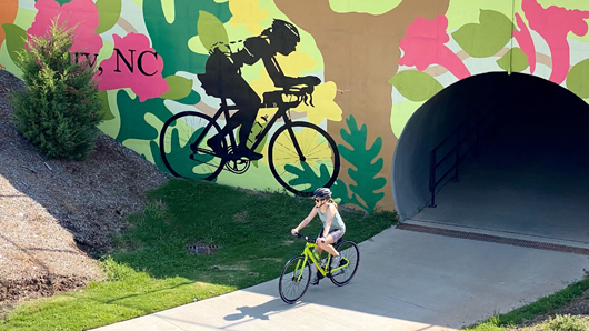 Woman riding a bike, coming out of a concrete tunnel with a giant bike mural painted on the exterior of the bridge