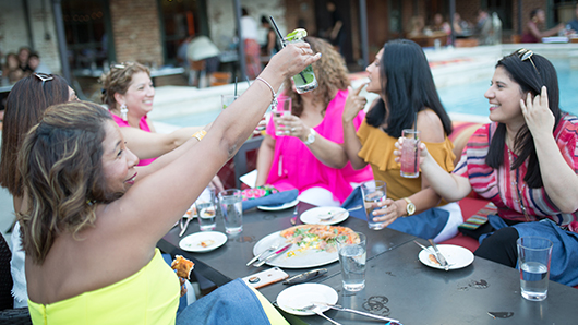 A group of women toasting at a restaurant outdors