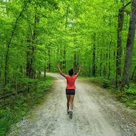 A woman running through a wooded trail with her hands up