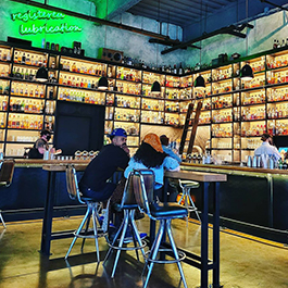 A couple sitting in the middle of a bar with lots of liquor bottles lining the walls, floor to ceiling