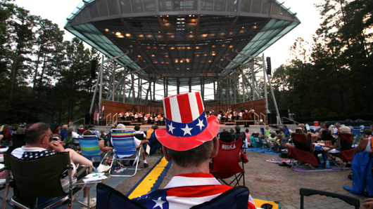 Man with a patriotic, American flag hat watching a concert at an outdoor amphitheater