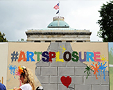 Mural in front of the N.C. State Capitol that says #Artsplosure