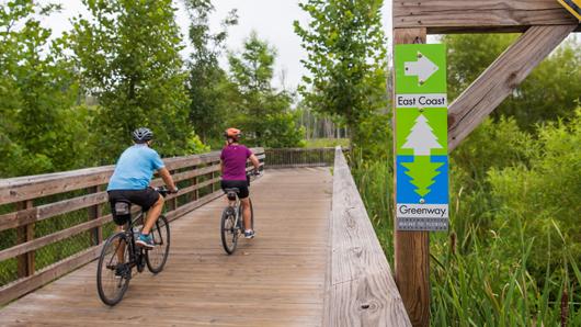 A couple biking across a wooden boardwalk on a greenway