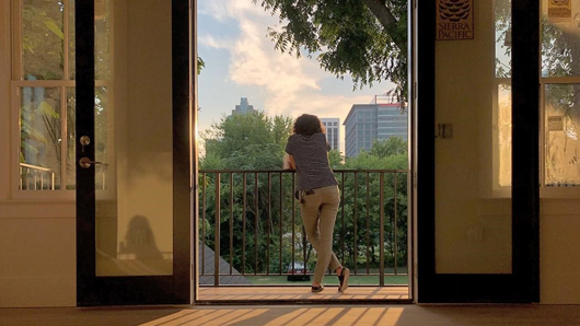 A hotel guest looking at the downtown Raleigh skyline from a balcony