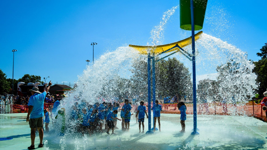 A huge, highly elevated bucket of water dropping water on kids at a splash pad
