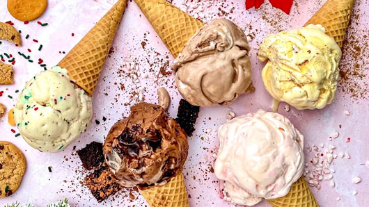 Photo of ice cream cones, with chocolate, vanilla and more flavors, on a pink table