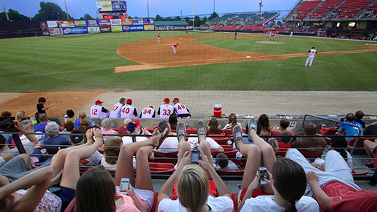 A crowd watching a baseball game in the early evening