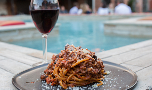 Close-up photo of a plate of spaghetti next to a glass of wine