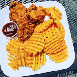 A plate of vegan chicken nuggets and waffle fries at Pure Juicery Bar