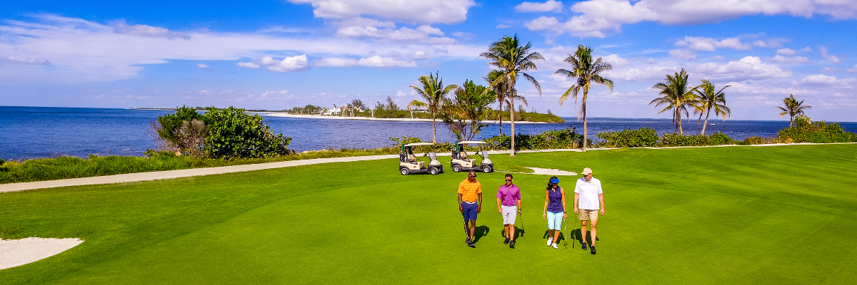 Group golfing on course overlooking the Gulf of Mexico